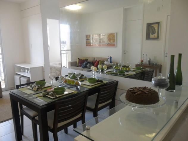Sala de jantar com mesa preta com tampo de vidro e cadeiras também pretas. O resto da sala é todo branco, ao fundo podemos ver a sala de tv.
